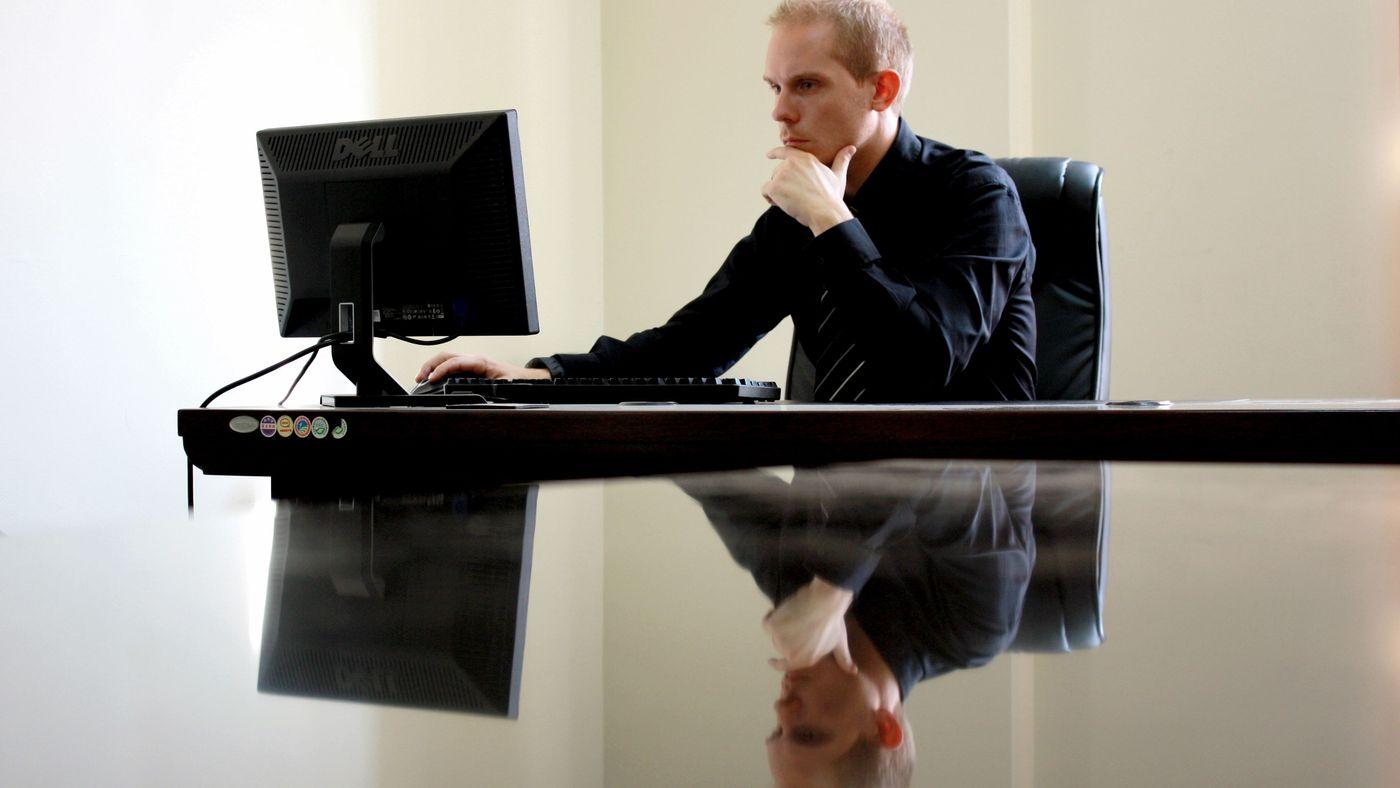 Mann sitzt vor Rechner